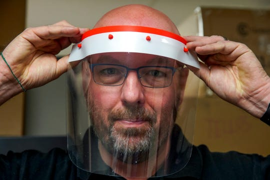 Mike Wilson, GIS Director, demonstrates how the 3D printed piece flexes and can be placed over the forehead at the Austin Peay GIS Center in Clarksville, Tenn., on Tuesday, March 24, 2020.