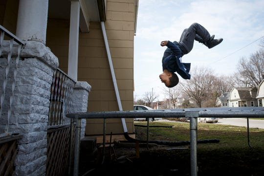 Alberto Torres, 7 of Des Moines, takes advantage of the sunlight and jumps on his trampoline on Tuesday, March 24, 2020, in Des Moines.