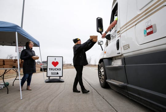 Brenda Neville of the Iowa Motor Truck Association in Des Moines, hands out a boxed lunch to a truck driver at a weigh station near Mitchellville, Iowa, on Tuesday, March 24, 2020.