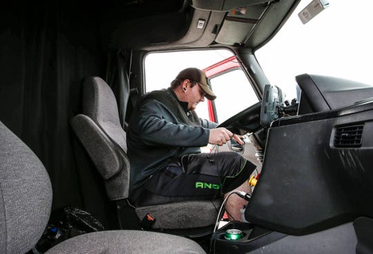 Ryan Hill, an over-the-road truck driver from Arkansas, climbs into his rig at a rest stop along Interstate 80 near Mitchellville on Tuesday.