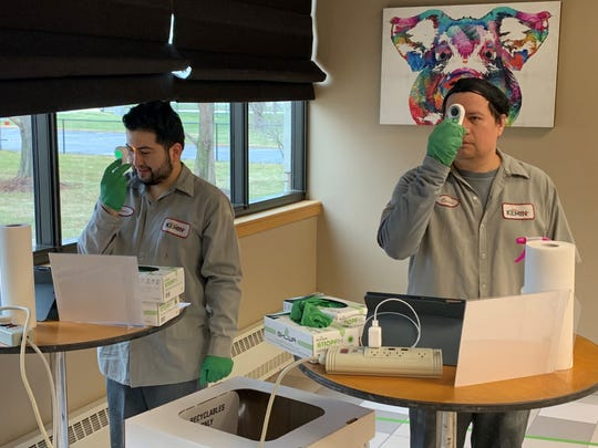 Kemin Industries production employees Rudy DePaz (left) and Oscar Luna take their temperatures before returning to work at the Des Moines global nutritional ingredient manufacturer.