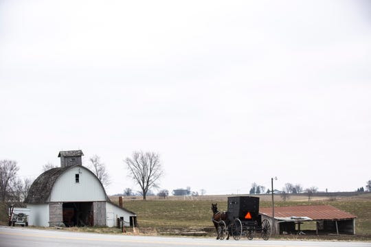 An Amish horse-drawn carriage rides along Highway 1 outside of Kalona, Tuesday, March 24, 2020, in Johnson County, Iowa.