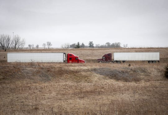 Trucks roll along Interstate 80 near Mitchellville, Iowa, on Tuesday, March 24, 2020.