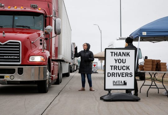 Janelle Stevens of the Iowa Motor Truck Association in Des Moines gives a thumbs up to a driver after handing out a boxed lunch at a weigh station near Mitchellville on Tuesday.