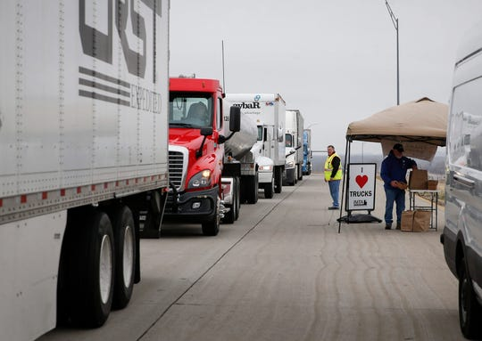 Truck drivers roll into a weigh station near Mitchellville, Iowa, for a free boxed lunch handed out by members of the Iowa Motor Truck Association on Tuesday, March 24, 2020.