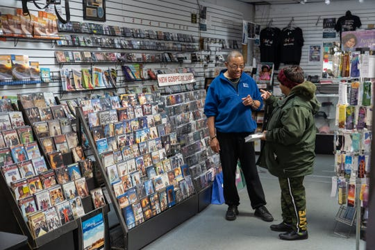 God's World owner Larry Robinson talks with Giselle Johnson of Detroit in his store on March 23, 2020, on the eve of temporarily closing as part of Gov. Gretchen Whitmer's executive order to help combat the spread of COVID-19.