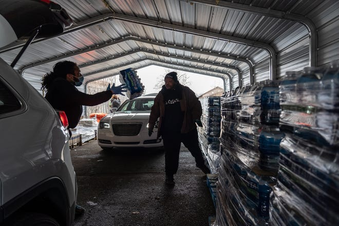 Volunteer Eric Bonner (left) of Flint loads cases of water into a car with the help of Edmund Merriwether of Flint during a water distribution for Flint residents through the United Way of Genesee County at Greater Holy Temple Church of God in Christ in Flint on March 19, 2020.