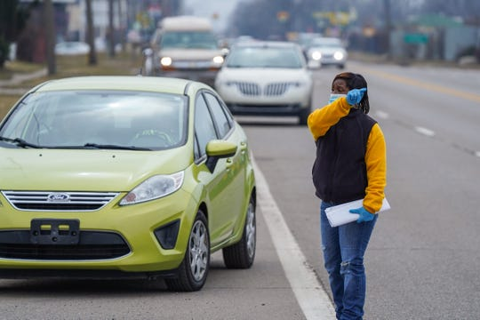 """R.L. Jones Community Outreach Center Director Latrece Davis directs a line of cars waiting to enter into a water distribution for Flint residents through the United Way of Genesee County at Greater Holy Temple Church of God in Christ in Flint on March 19, 2020. """"It's an increase because they're thinking that everything is about to stop with this virus. By us not having waters in the stores everybody's coming to the free water giveaway,"""" Jones said."""