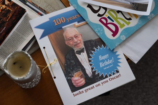 A booklet in honor of Oscar Paskal's 100th birthday sits on a table in the living room of his home in Detroit's Indian Village neighborhood on March 23, 2020.