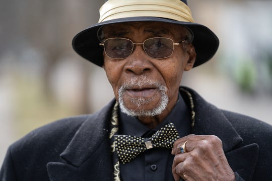 """Houston Pritchett, 100, of Detroit, stands outside of his home on March 23, 2020. """"I've been through a lot of stuff. This is the worst I've ever seen. All through the depression, World War II, everything. This tops them all,"""" Pritchett said about the Coronavirus."""