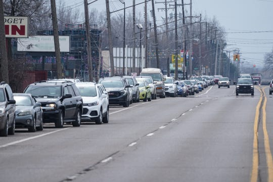 A line of cars waits to enter into a water distribution for Flint residents through the United Way of Genesee County at Greater Holy Temple Church of God in Christ in Flint on March 19, 2020, after a semi carrying the water was late arriving.