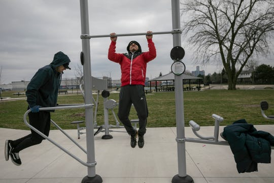 Laid off contractors Jose Morales, 23, of Detroit, left, works out with his friend and fellow co-worker Carlos Rodriguez, 22, of Detroit on March 24, 2020, in a park in Detroit. The two were looking for an outlet since their gym has been shut down due to Novel Coronavirus threat.