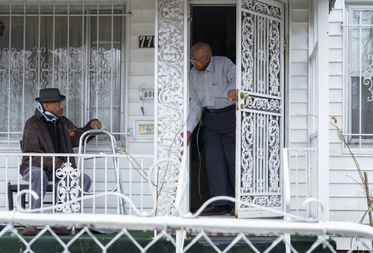 """Leonard Edwards, 70, of Flint sits on the front porch near his father Will Edwards, 97, at his dad's home in Flint's north side on March 20, 2020. Leonard, who recently had vertebrae surgery and has a cough, doesn't go into his father's home to avoid him catching anything from him due to his age. His father has a bad knee and an irregular heartbeat.""""It's one thing after another,"""" Leonard said about having recently dealt with the Flint Water Crisis to now worrying about COVID-19. """"I got to keep him on bottled water. I don't trust the water. I didn't trust it and I ain't going to trust it. I can't wait in line for hours to get it. By the time I get up there they're out,"""" he said, about going to water distribution sites for his father to avoid going around town looking water that might be low in stock at stores."""