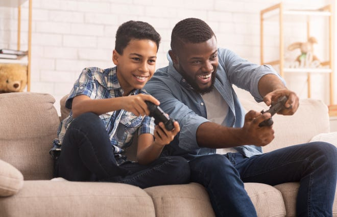 Cheerful Black Boy Competing In Video Games With His Father, Sitting On Sofa At Home