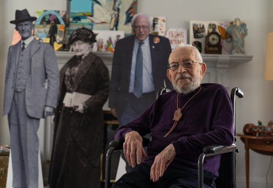 Oscar Paskal, 100, of Detroit sits in the living room of his home in Detroit's Indian Village neighborhood on March 23, 2020. Paskal, who became interested in the labor movement after reading about the Flint sit-down strike as a high school student in New York, is joined by life-sized images of people-past and present-who have earned his respect. From left, Eugene V. Debs, Mother Jones and Bernie Sanders.