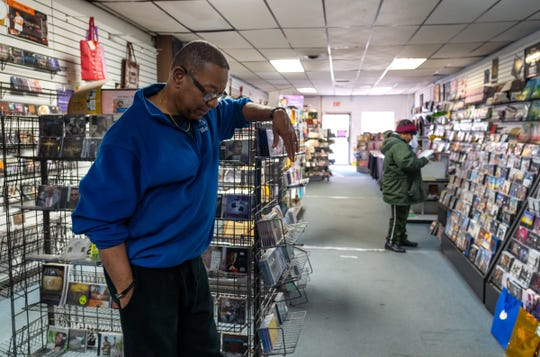 God's World owner Larry Robinson, owner of God's World on West Seven Mile, stands in his store on March 23, 2020, on the eve of temporarily closing his small business to comply with Gov. Gretchen Whitmer's executive order to help combat the spread of COVID-19.
