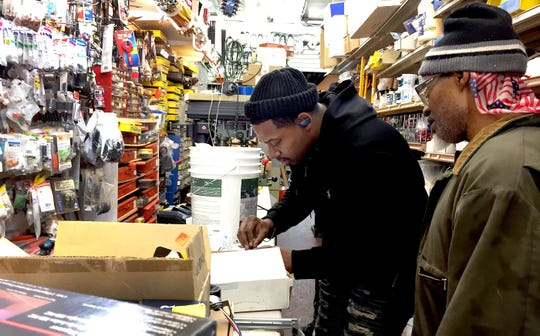 Javari Tinnon, center, owner of Hardware Express in Detroit, rebuilds part of a faucet for a customer the day before closing his store for a few weeks under Gov. Gretchen Whitmer's stay-at-home order.