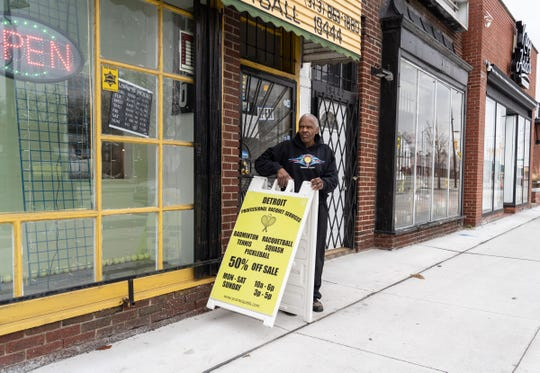 Professional Racquet Services owner Michael Banks takes his sign in towards the end of the day on March 23, 2020, on the eve of temporarily closing his Detroit business as part of Gov. Gretchen Whitmer's executive order to help combat the spread of COVID-19.