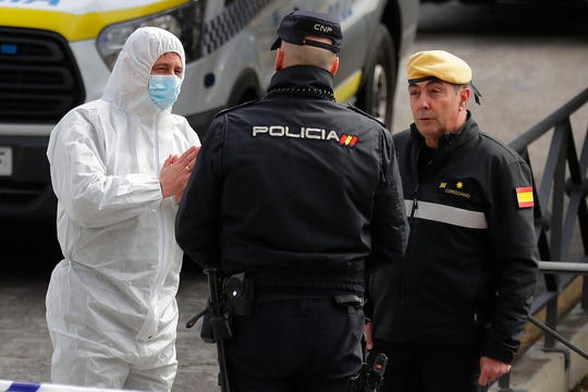 A member of UME, left, talks with a police officer at a ice-skating rink in Madrid, Spain, Tuesday, March 24, 2020. Madrid's ice-skating rink is now being used as a makeshift morgue given the rapid increase in deaths in the Spanish capital owing to the Covid-19 outbreak.