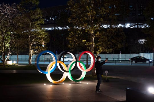 "A man takes a selfie with the Olympic rings in front of the New National Stadium in Tokyo, Tuesday, March 24, 2020. IOC President Thomas Bach has agreed ""100%"" to a proposal of postponing the Tokyo Olympics for about one year until 2021 because of the coronavirus outbreak, Japanese Prime Minister Shinzo Abe said Tuesday."