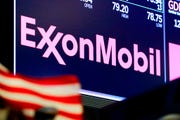 In this April 23, 2018, file photo, the logo for ExxonMobil appears above a trading post on the floor of the New York Stock Exchange. Exxon Mobil Corp. has slowed rates at oil refineries in Texas and Louisiana due to a historic plunge in gasoline demand and prices.