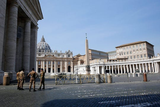 Italian soldiers patrol the area in front of an empty St. Peter's Square, at the Vatican, Sunday, March 22, 2020.