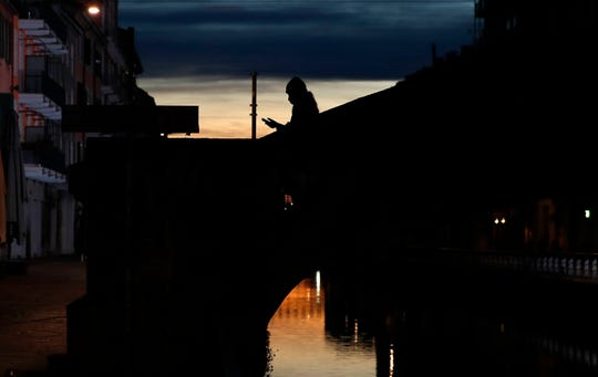 A woman wearing a face mask checks her phone as she walks at the Naviglio Grande canal in Milan, Italy on March 10.