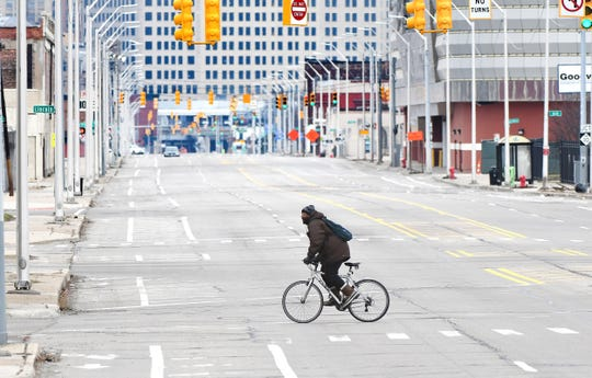 A bicycle rider crosses Grand River Avenue near Rosa Parks Boulevard as empty streets are seen throughout  Detroit on Tuesday, March 24, 2020.