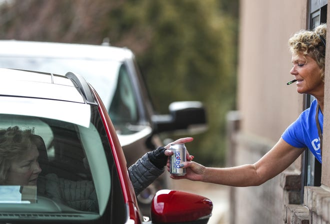 Denise VanLanen, right, hands Terri Jolly, left, a Pepsi on Tuesday at Crystal Coffee Cafe and Beanery in Ashwaubenon. Jolly ordered a breakfast sandwich, coffee and soda from the drive-thru window.