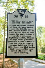 "The marker erected in 2016 explaining the burial ground for enslaved peoples and convict laborers on Clemson University's campus. It reads: ""African Americans enslaved at Fort Hill were buried along the hillside below the Calhoun family plot in graves marked only by field stones. The exact number of burials is unknown. Beginning in 1890, Clemson College leased prisoners, primarily African Americans, from the state to construct campus buildings. Until 1915, those who died during their incarceration were buried adjacent to the slave cemetery."""