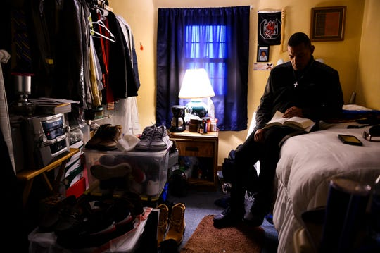 Hassan Salaam, 51, a recovering opioid user, reads a recovery book in his room at Freedom House Monday, March 23, 2020.