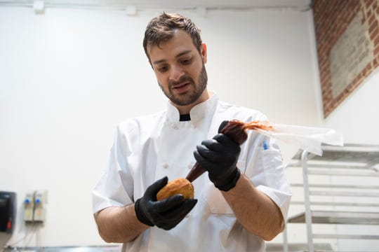Chef Vincent Caradonna injects filling into donuts at Le Petit Croissant in the morning Saturday, Mar. 21, 2020.