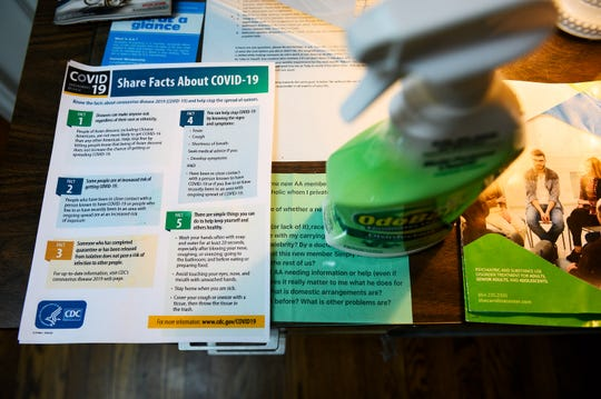 An informational sheet on COVID-19 is displayed next to a spray bottle of disinfectant at Freedom House Monday, March 23, 2020,
