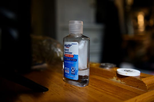 A bottle of hand sanitizer sits in front of a row of recovery chips in Hassan Salaam's room at Freedom House Monday, March 23, 2020,