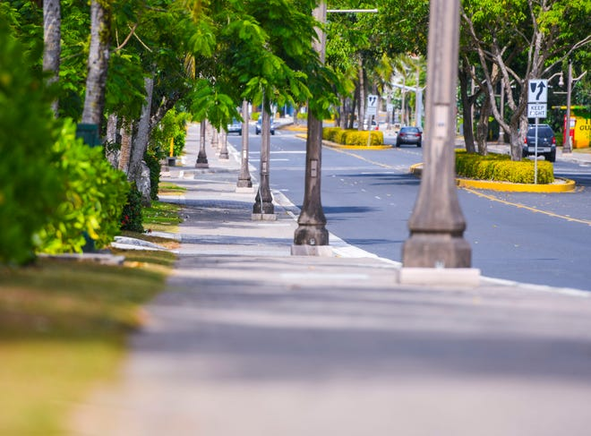 A nearly empty San Vitores Road and a sidewalk in Tumon is shown in this March 24 file photo.