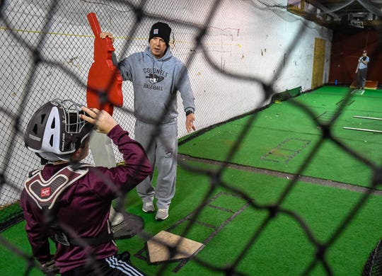 Henderson County baseball coach Adam Hines, who has polycystic kidney disease and is in need of a kidney transplant, works with catcher Dalton Overfield during a preseason baseball practice Wednesday, February 26, 2020.