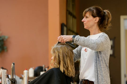 Becky Rasmussen, owner of Love's Hair Etc. & Spa, curls Olivia Vandenberg's, 7, hair, Tuesday, March 24, 2020 in Lafayette.
