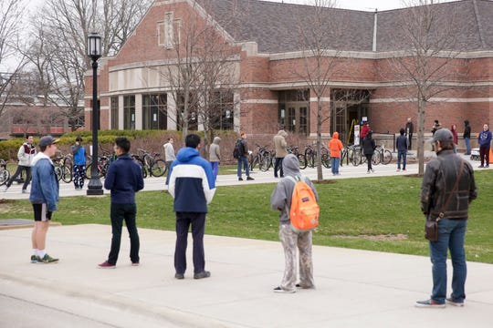 Students line the sideway around Purdue University's Krach Lawn as they wait to enter the Wiley Dining Hall for lunch, Tuesday, March 24, 2020 in West Lafayette.