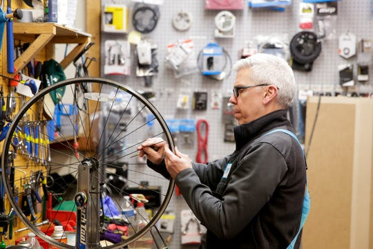 David Meadows, owner of Hodson's Bay Company, repairs a wheel in the back of his Levee Plaza shop, Tuesday, March 24, 2020 in West Lafayette.