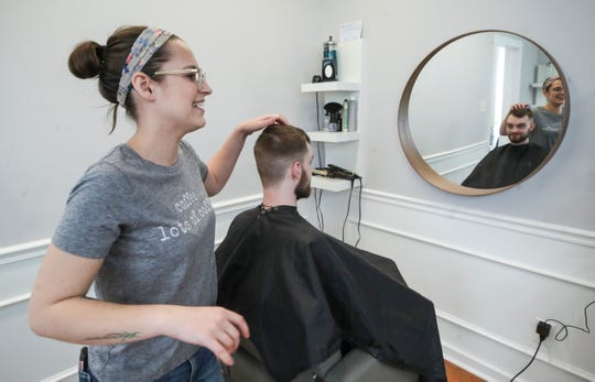 """Alexis Mattingly works on customer Thomas Coyle's haircut at her Serene Salon in Jeffersonville on Court Avenue Tuesday. """"I'm trying to stay positive through all this,"""" Mattingly said. """"Stress isn't going to change anything. Just take it day by day."""" March 24, 2020"""