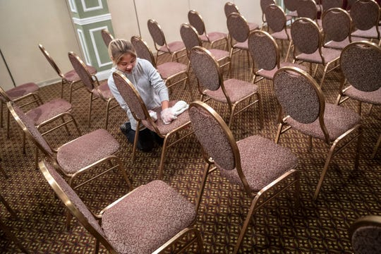 Brown Hotel employee Jessie Bisa cleans conference room chairs on Tuesday. Normally Bisa works in the hotel's bar.