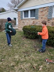 "Ryan and Grayson Steiner unwind holiday lights in their yard in Holt on Tuesday, March 24, 2020. The family put up holiday lights usually reserved for Christmas in an effort to brighten the neighborhood during Michigan's ""stay home, stay safe,"" order amid the coronavirus pandemic."