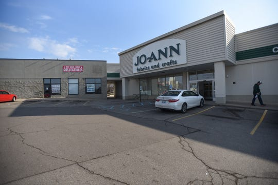 A man leaves JoAnn Fabrics on West Saginaw Street in Lansing on Tuesday, March 24, 2020.