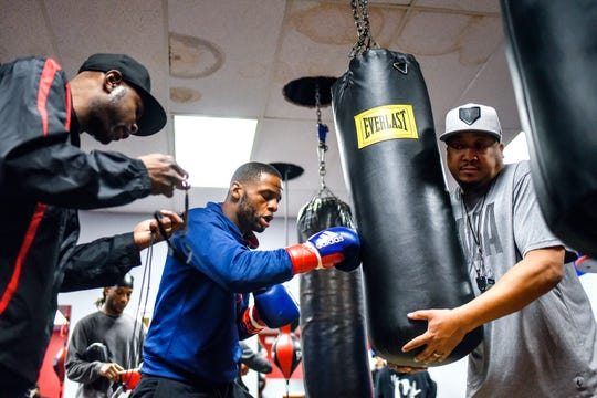 Joseph Hicks Jr., center, trains with coach Wayne 'Uncle T' Easley, left, and coach Phats on Thursday, Feb. 27, 2020, at Team GLASS gym in Lansing. Hicks will represent USA Boxing at middleweight in qualifications for the 2021 Summer Olympics.