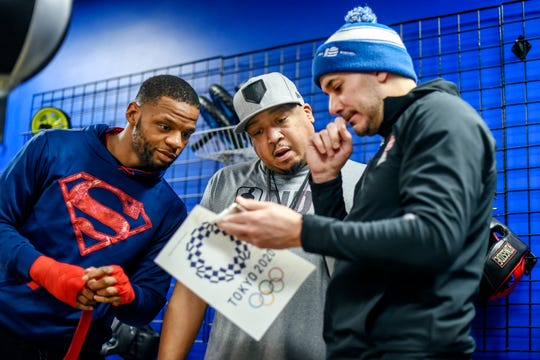 Joseph Hicks Jr., left, along with coach Phats, center, and  trainer Steve Maniaci look over information about the 2020 Summer Olympics on Thursday, Feb. 27, 2020, at Team Glass Boxing gym in Lansing. Hicks will represent USA Boxing at middleweight in qualifications for the 2021 Summer Olympics.