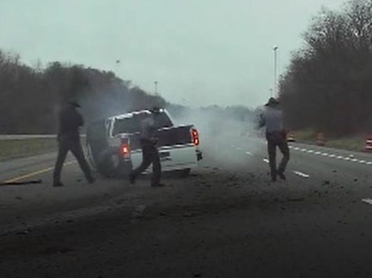 Troopers with guns drawn approach a pickup after it crashed on southbound  I-71 in Richland County.
