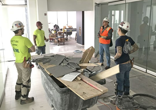 A group of construction workers at the BMO Tower job site in downtown Milwaukee practice social distancing on Tuesday. Some construction projects could be stopped by the new stay at home order from Gov. Tony Evers.