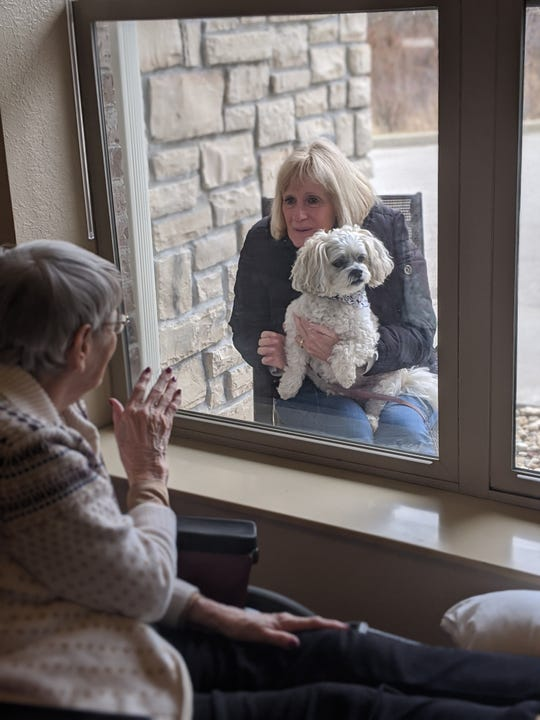 Donna Grode of Waukesha visits her mother at the window at  Heritage Senior Living Community in Elm Grove.