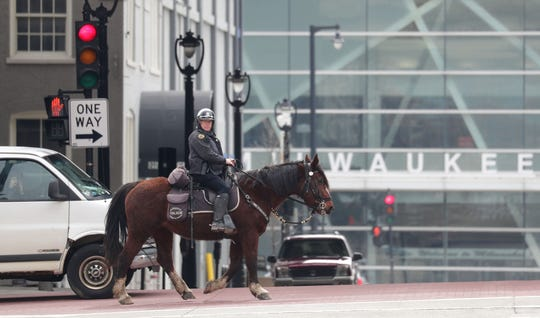 A Milwaukee police officer patrols on horseback along West Clybourn Street near North Sixth Street in Milwaukee. Crime numbers have dropped in the city since the coronavirus outbreak.