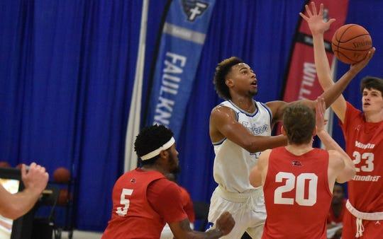 Faulkner guard CJ Williamson drives to the basketball against Martin Methodist.